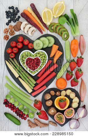 Healthy nutritional food concept with fresh vegetables, fruit, spice and nuts on rustic background. Health food concept high in omega 3 fatty acids, antioxidants, anthocyanins, minerals & vitamins.