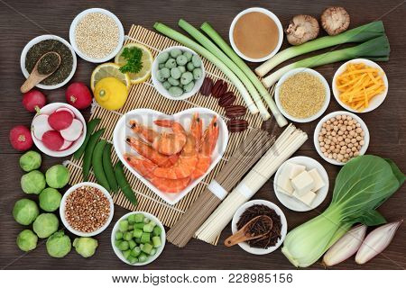 Macrobiotic health food concept with seafood, soba and udon noodles, miso, tofu, kuchika tea, wasabi nuts, vegetables, legumes and grains with food high in protein, antioxidants, vitamins and minerals