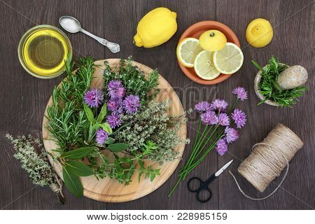 Herb seasoning with fresh herbs also in flower with lemon fruit and olive oil, with string and scissors to hang and dry leaves. On rustic oak wood background, top view.