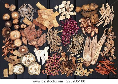 Large chinese herb selection used in traditional herbal medicine on dark wood background. Top view.