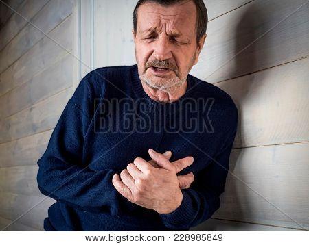 A heart attack. Elderly man, his hands near the heart
