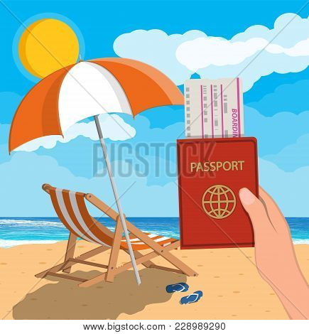Passport And Airplane Ticket In Hand. Landscape Of Wooden Chaise Lounge, Umbrella, Flip Flops On Bea