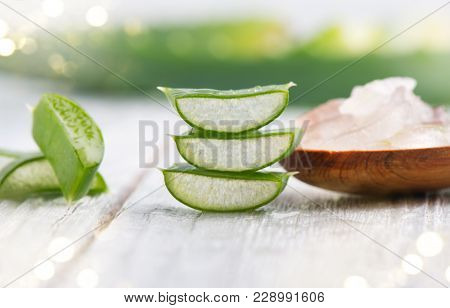 Aloe Vera gel closeup. Sliced aloevera leaf and gel, natural organic cosmetic ingredients for sensitive skin, alternative medicine. Organic Skin care concept. On white wooden background