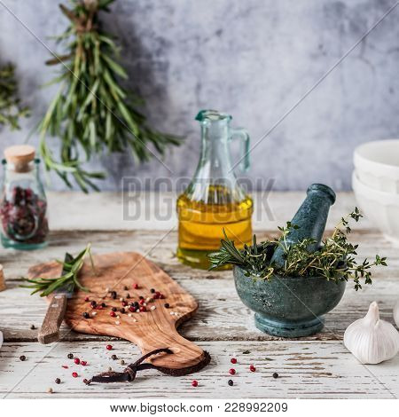 Herbs And Spices, Mortar And Pestle, Thyme, Posemary, Olive Oil, Salt Crystals And Whole Peppercorns