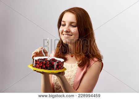 Young Attractive Red-haired Girl Holding A Cake With Candle And Makes A Wish On The Birthday. Her Fa