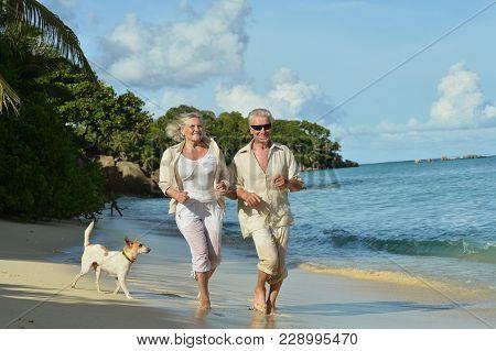 Happy Elderly Couple Running On Sandy Beach Near Tropical Resort