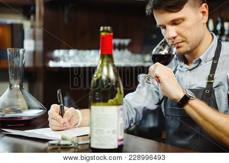 Male Sommelier Tasting Red Wine And Making Notes At Bar Counter. Bottle Of Wine Nearby. Professional
