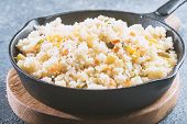 Cous Cous whit meat and vegetables in frying pan over gray stone background poster