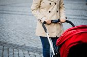 Young mother walking with baby carriage at the street. Mother with a stroller walks down the street poster