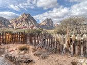 Old rickety wooden picket fence in an arid semi-desert landscape with broken wagon wheel and rocky mountain peaks rising from the valley floor poster