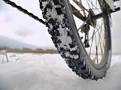 Rear wheel detail of mtb. Snow flakes melting on dark off road tyre. Winter weather in the field. poster
