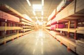 Blurred lumber yard at home improvement retail store in America. Rack of fresh mill, cut wood timber, pegboard, plywood, osb paneling, mdf in warehouse of hardware store. poster