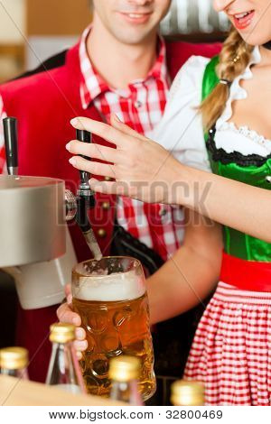 Young woman drawing beer in restaurant or pub, she is the innkeeper