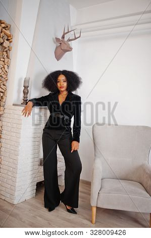 Stylish African American Woman In Black Posed At Room Against Fire Place.