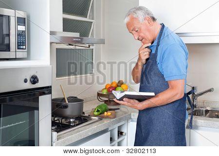 Senior man preparing food with the help of recipe book