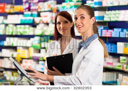 Pharmacist with female assistant in pharmacy standing at the cashpoint