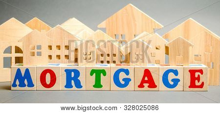 Wooden Blocks With The Word Mortgage And Miniature Houses. Loan Form With A Pledge. Buying Real Esta