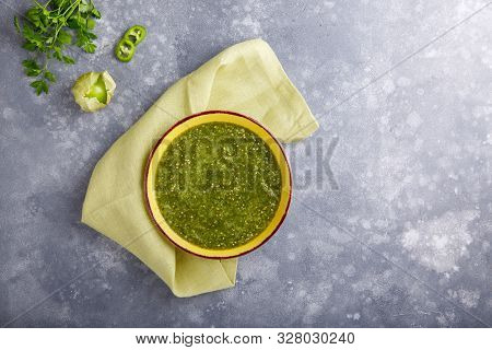 Tomatillo Salsa Verde. Bowl Of Spicy Green Sauce On Gray Table, Mexican Cuisine. Top View. Copy Spac