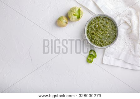 Tomatillo Salsa Verde. Bowl Of Spicy Green Sauce On White Table, Mexican Cuisine. Top View. Copy Spa