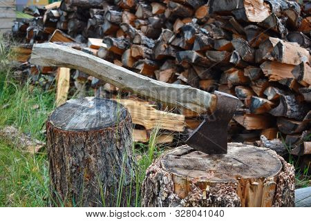Old axe with wooden handle on stub. To cut and prepare firewood for winter. Woodpile with firewood at fence. Wood heating in village. poster