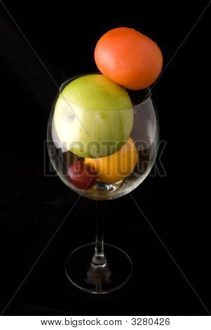 A cup of fresh fruits including red tomato green apple orange and red grape on black background poster