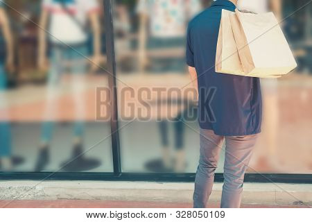 Man Holding Shopping Bags Looking At Shop Window
