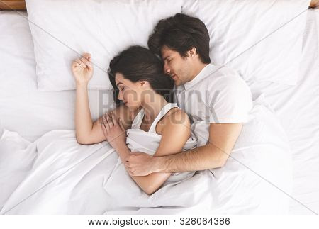 Loving Married Couple Sleeping In Bed And Hugging, Love And Tenderness Concept, Top View