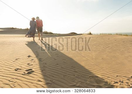Husband And Wife Strolling On Seashore During Vacation. Back View Of Young Couple Strolling On Sandy