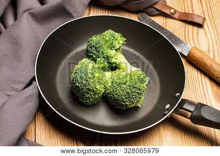 Brocoli In A Frying Pan On A Wooden Table