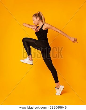Fitness. Young Lady Jumping During Cardio Workout On Yellow Studio Background. Side View