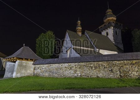 View On Ancient Gothic Church Of The Presentation Of The Lord  At Night,  Outside. Village Smrečany,