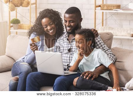 Online Shopping. Happy Black Mother, Father And Daughter Using Laptop And Credit Card, Buying Goods