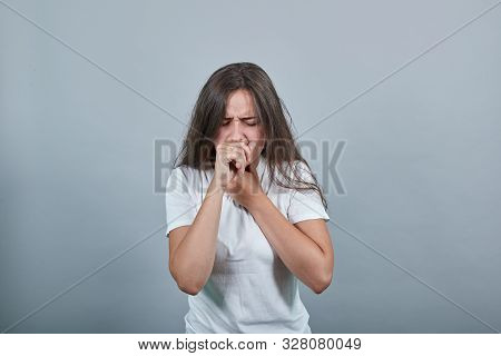 Young Caucasian Girl With White Shirt Is Suffering With Cough And Feeling Bad. Person Holds His Hand