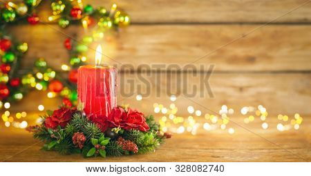 Burning Christmas red candle and  festive Christmas arrangement on a wooden table. Christmas advent