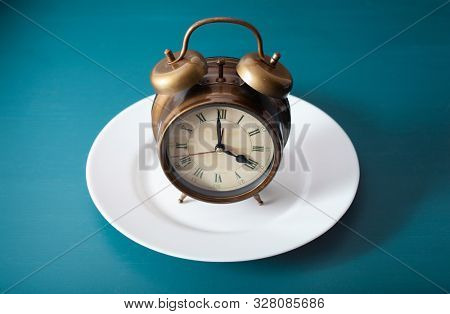 concept of intermittent fasting, ketogenic diet, weight loss. alarmclock on plate