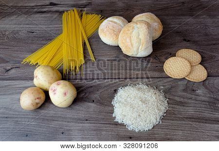 Common Bad Carbohydrates To Avoid Such As White Bread, Pasta, Rice, Potatoes And Buscuits Laying On