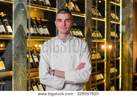 Young Handsome Cook Chief Posing In Modern Restaurant Interior At Wine Refrigerator Background.