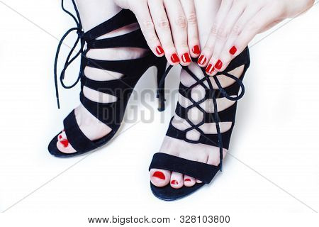 Fashion Concept People: Woman With Red Nails Manicure Pedicure Tying Shoelaces On Hight Heel Shoes I