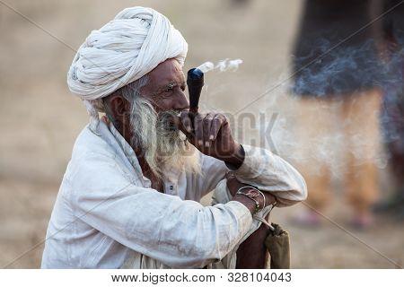 Pushkar, Rajasthan/india - November 20, 2018: Rajasthani Man Smoking Hashish In A Chillum (clay Pipe