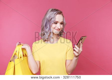 Young Stylish Woman In The Yellow T-shurt Holding Phone And The Same Solor Packege Isolated.