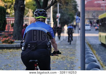 A Female Police Officer On A Bicycle Patrols The Streets In Ukraine. A Female Policeman In A Blue Un
