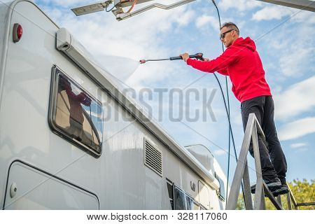 Post Season Rv Motorhome Camper Van Washing Using Pressure Washer. Caucasian Motor Coach Owner.