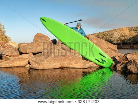 senior male paddler is launching asn inflatable stand up paddleboard from a rocky shore of mountain lake - Horsetooth Reservoir in northern Colorado