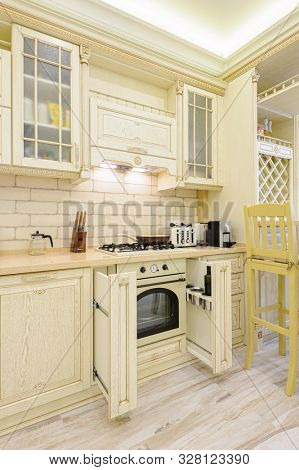 Spacious and luxury modern beige kitchen in Provence style, so,e drawers and dishwasher open