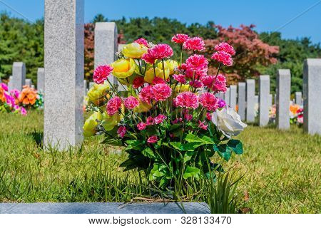 Closeup of bouquet of fresh cut pink and yellow flowers in front of headstone at in local cemetery. poster