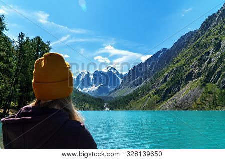 A Girl With Camping Clothes On The Shore Of A Wonderful Lake Looking At The Mountain Peaks. A Focus