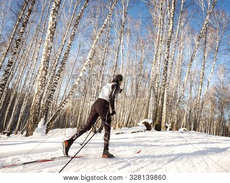 Skiing During Training In The Winter Forest On A Sunny Day.