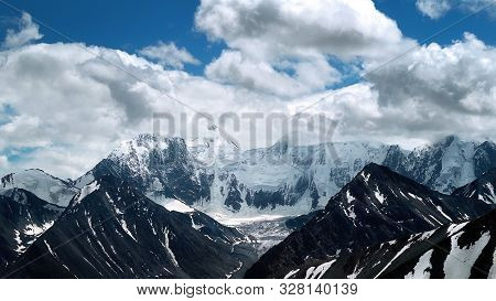 A Snowy Mountain Peak In The Clouds. The Highest Mountain Of Altai Belukha, Siberia.