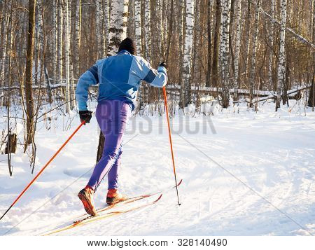 A Skier With Beautiful Equipment In The Winter Forest On A Sunny Day At Workout.