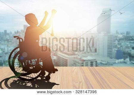 Disabled Person Silhouette Winners Hand Holding Gold Medal Top Of Wheelchair Sunset With City Backgr